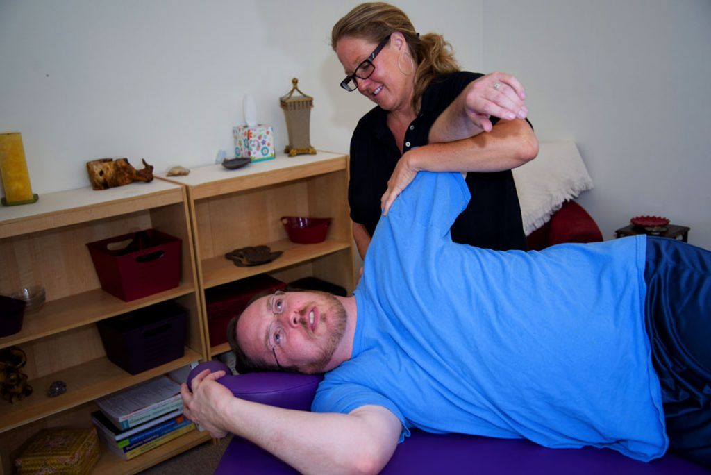 massage therapist stretching shoulder pain